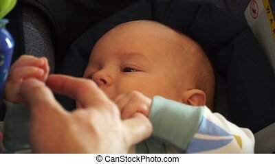 Close-up of a child playing with his father's hand