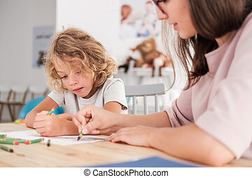Close-up of a child with an autism spectrum disorder and the therapist by a table drawing with crayons during a sensory integration session.