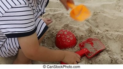 Close up of a child's hand playing sand toys crop