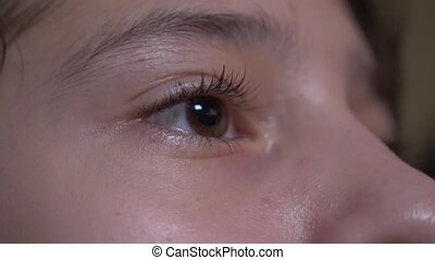 Close-up of a child's human eye. the girl looks closely at the TV screen while watching the video. 4k, slow motion