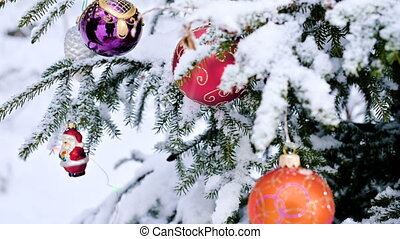 Close-up of a Christmas toy on a snow-covered lively tree in...