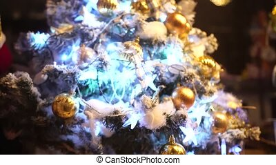 Close-up of a Christmas tree in the snow with a flashing garland.