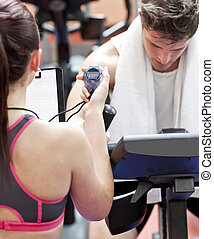 Close-up of a coach using a chronometer while man is doing physical exercises in a fitness centre