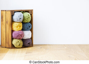 Close-up of a colorful yarn stack in a wooden crate by a white wall and copy space. Real photo.