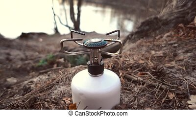 Close-up of a compact tourist gas burner burning propane...