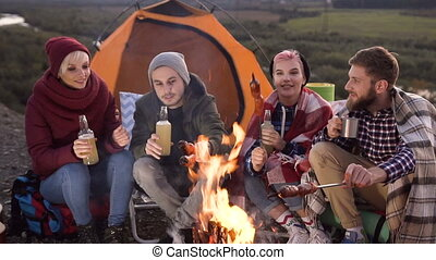 Close-up of a company of four caucasian young friends having a picnic by the mountains, they are chatting, laughing, drinking beer and bake sausages on bonfire. Being happy, young and free, tourism concept