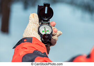 close-up of a compass in the hand of a lost tourist in a winter forest