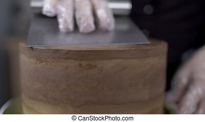 Close-up of a confectioner is leveling a cake using a cake ...