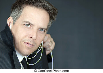 Close-up of a confident businessman wearing headphones looks sideways to camera.