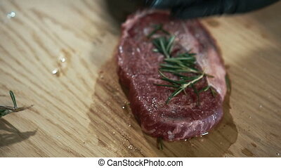 Close-up of a cook sprinkles a piece of raw meat with herbs.