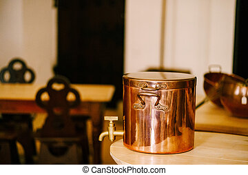Close-up of a copper liquid container with a faucet on a wooden countertop in the kitchen.