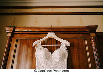 Close-up of a corset of a bride's wedding dress on a hanger by a wooden cabinet.