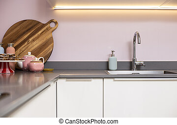 Close-up of a counter and modern kitchen. steel sink with pink wall and decoration modern light interior