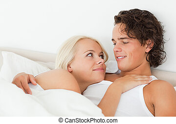 Close up of a couple lying on a bed hugging