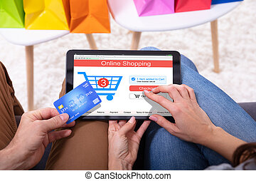Close-up Of A Couple Shopping Online On Digital Tablet