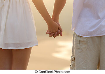 Close up of a couple walking and holding hands on the beach