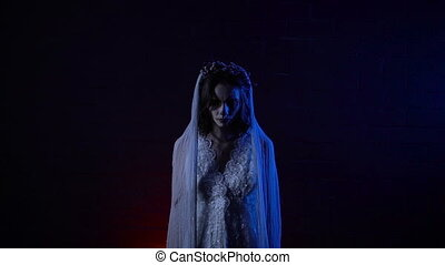 Close up of a creepy scene with phantom of a bride dressed in white dress and veil who is standing and staring at the camera. Young ghost of bride is rising her hands up twice like wings.