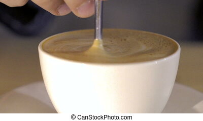 Close up of a cup of coffee in which mixing the tasty foam. Slowly