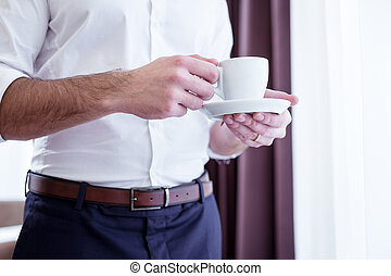 Close up of a cup with coffee in male hands