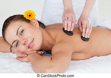 Close up of a cute brunette enjoying a hot stone massage