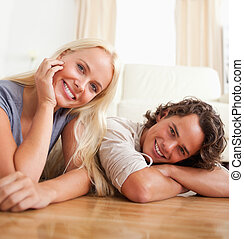 Close up of a cute couple lying on the floor