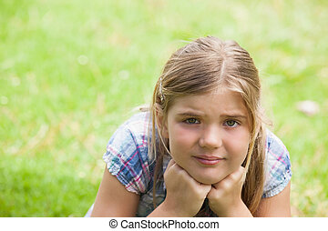 Close-up of a cute girl lying on grass at park
