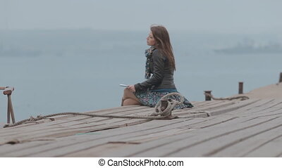 Close up of a cute girl sitting on the dock looking at the sea, where the boat floats