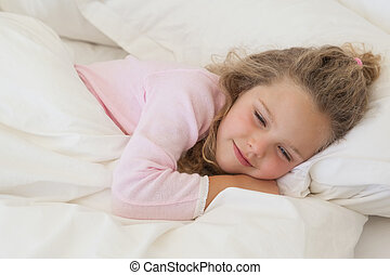 Close-up of a cute girl sleeping in bed