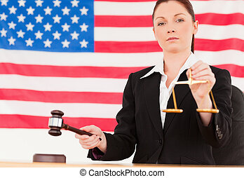 Close up of a cute judge knocking a gavel and holding scales of justice with an American flag in the background