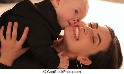 Close-up of a cute little boy kissing his beloved mother.