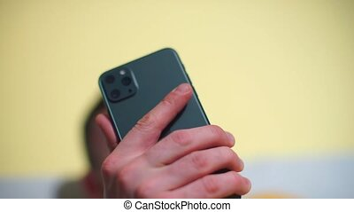 Close-up of a dark smartphone in the hands of a man.