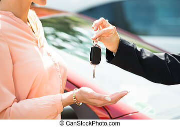 Dealer Giving Car Key To Woman