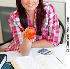 Close-up of a delighted caucasian woman holding an apple sitting in the kitchen at home