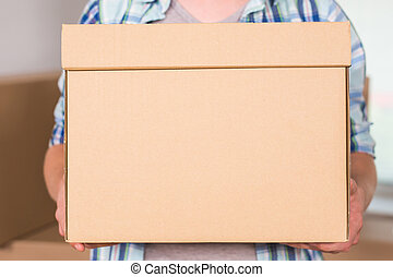 Close-up Of A Delivery Man Holding Cardboard Box