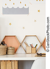 Close-up of a desk with pen cups, shelves in the shape of honeycombs and star stickers on the wall