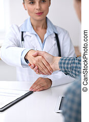 Close up of a doctor woman shaking hands with her male patient. Medicine and trust concept