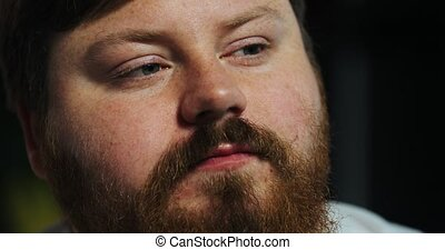 Close-up of a face of eating fat man looking at the TV-set,...