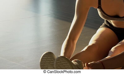 Close-up of a female athlete on floor stretches leg muscles...
