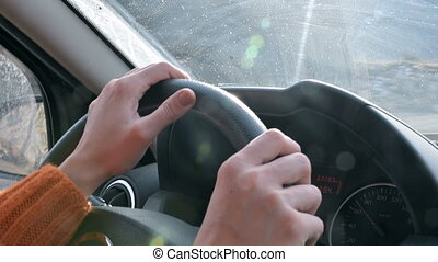 Close-up of a female hand in an orange sweater driving a car...