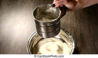 Close-up of a female hand sifting flour with a sieve mug in...