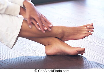 close-up of a female person´s hands and feet; wooden floor; white leisure wear; frontside