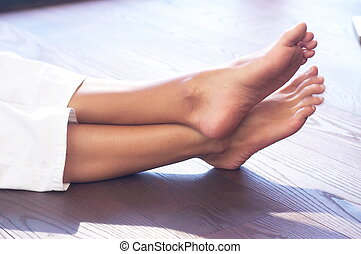 close-up of a female person?s feet; wooden floor; white leisure wear;