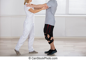 Physiotherapist Giving Support To A Male Patient
