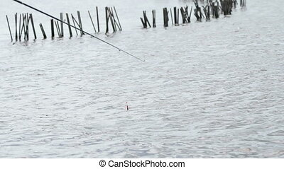 Close-up of a fishing rod and a red floater - Close-up of a...