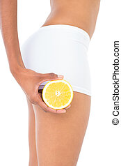 Close up of a fit woman carrying half an orange