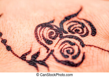 Close up of a Flower Design Painted with Black Henna to the Skin