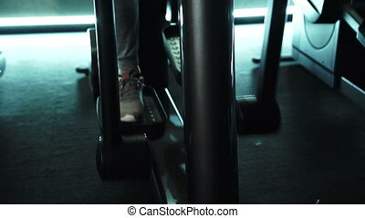 Close-up of a foot on an elliptical training machine in the gym.