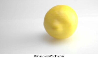 Close up of a fresh ripe lemon spinning on the table on white background.