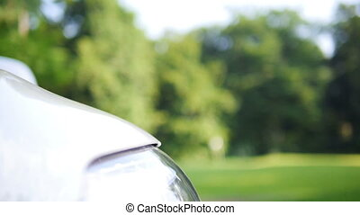 Close up of a front reflector of a white car standing...