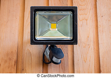 Close up of a garden sensor light fixed to a wooden wall
